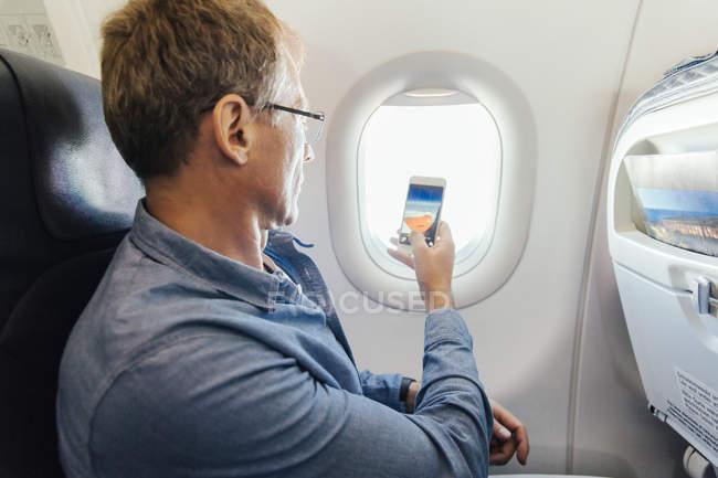 Photo prise de l'homme avec son téléphone portable par la fenêtre alors qu'il volait à bord d'un avion — Photo de stock