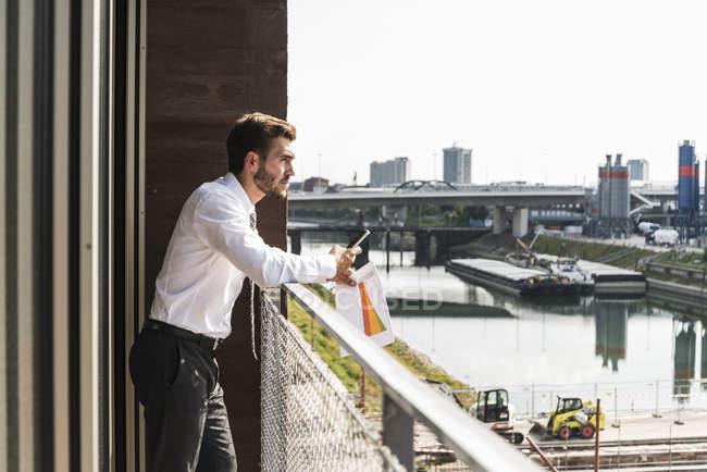 Jeune homme d'affaires debout sur le balcon regardant la vue — Photo de stock