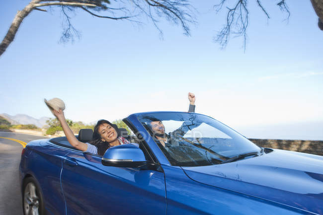 Happy couple riding in a convertible — Stock Photo