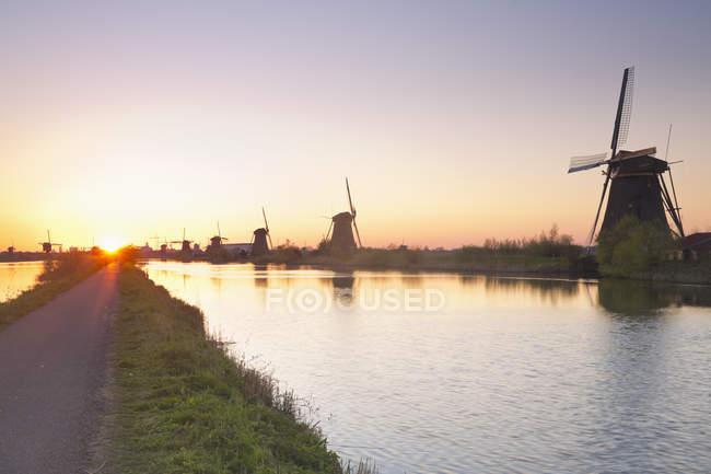 Netherlands, Kinderdijk, Kinderdijk wind mills at twilight over water — Stockfoto