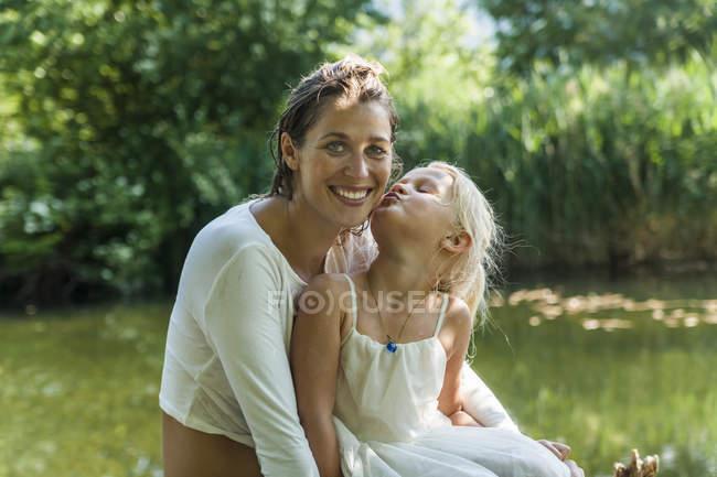 Дівчина цілуватися матері на озері — стокове фото
