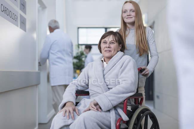 Пацієнт в інвалідному візку і внучка в лікарні коридор — стокове фото