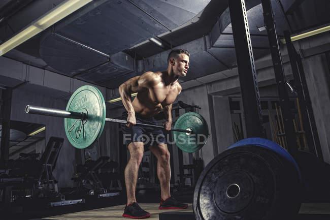 Тяжёлая атлетика с штангой в тренажерном зале — стоковое фото