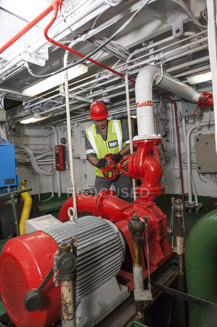 Adult caucasian man working in engine room on a ship — Stock Photo