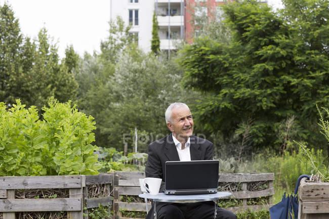 Geschäftsmann sitzt mit Laptop und Tasse Kaffee zwischen Hochbeeten — Stockfoto