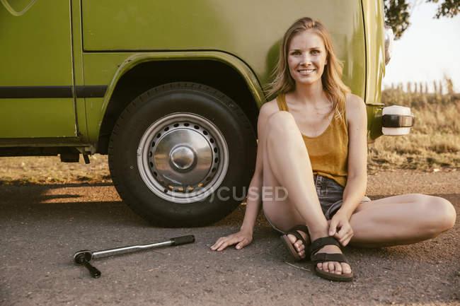 Mulher sentada ao lado de uma chave de torque no van a sorrir — Fotografia de Stock