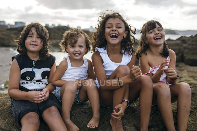 Spain, Gijon, group picture of four little children sitting at rocky coast having fun — Stock Photo