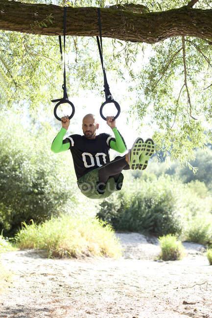 Человек делает тренировки Crossfit на кольца, висит на ствол дерева — стоковое фото