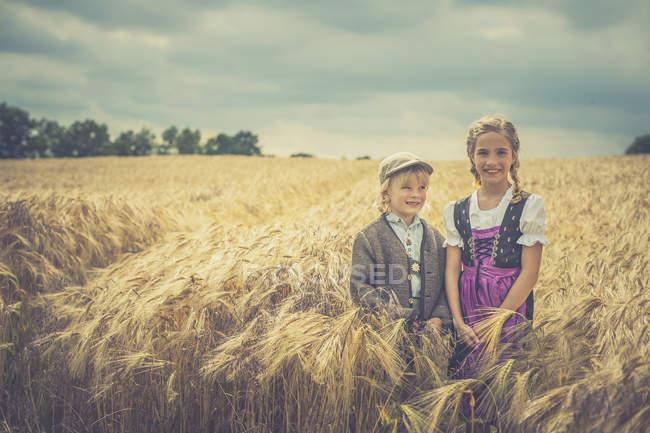 Two children standing in a grain field — Stock Photo