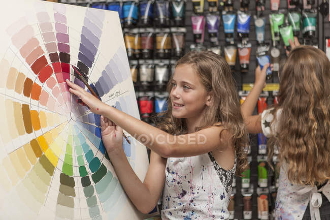 Girls in an art class by the color scale and paint tubes — Stock Photo