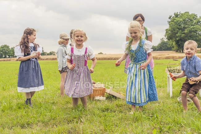 Bambini in costumi tradizionali balli su un prato — Foto stock