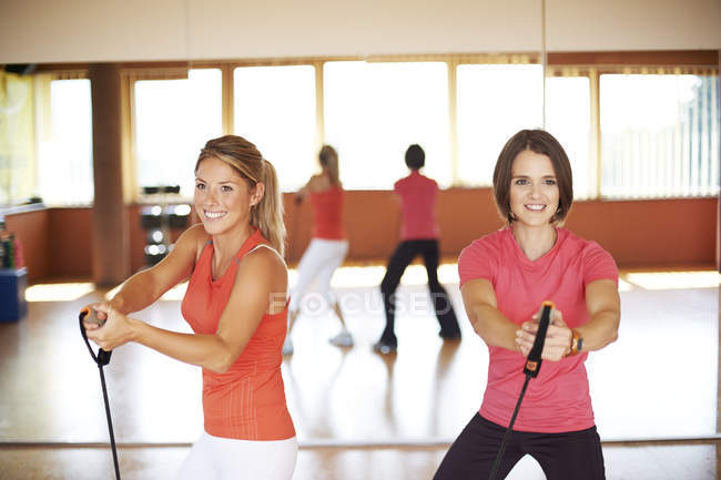 Two women doing suspension training in fitness studio — Stock Photo