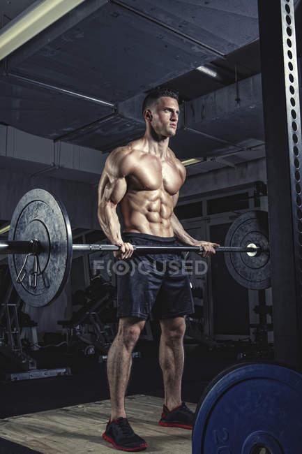 Levantamiento de pesas físico atleta con barra en el gimnasio - foto de stock