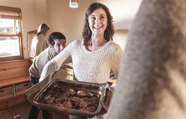 Lächelnde Frau serviert Essen in moderner Küche — Stockfoto