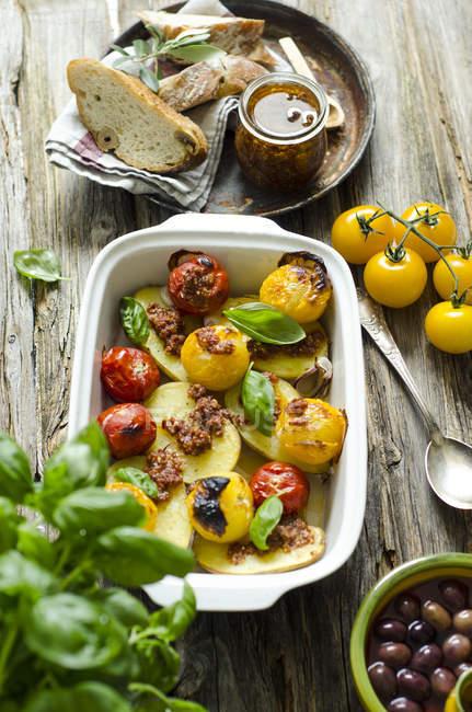Жареный картофель с томатным песто, помидорами и базиликом листья в выпечки на дереве — стоковое фото