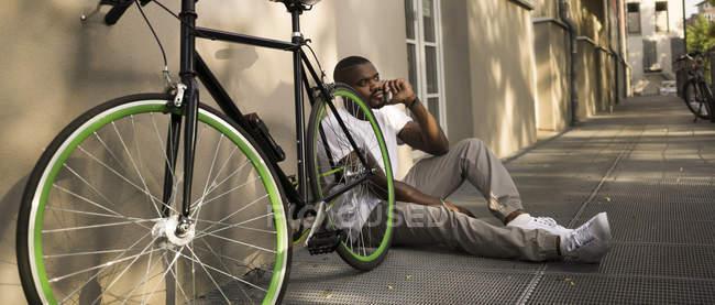 Homem sentado ao lado da bicicleta — Fotografia de Stock