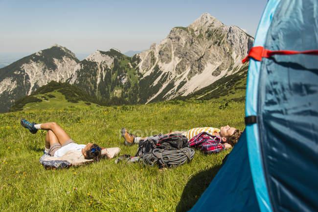 Áustria, Tirol, Tannheimer Tal, jovem casal descansando ao lado da tenda no prado alpino — Fotografia de Stock