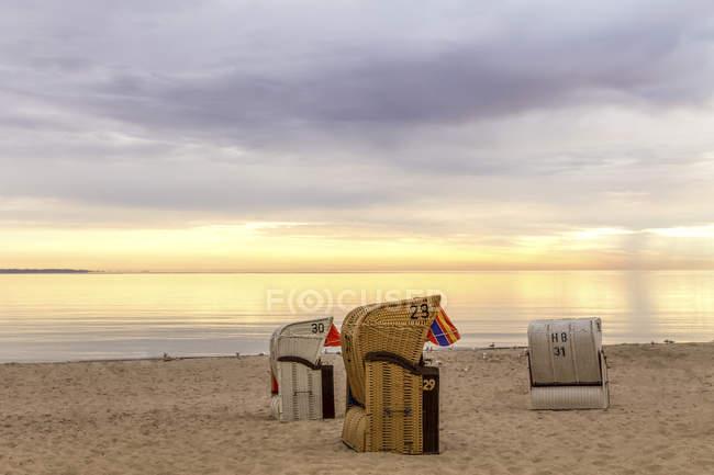 Deutschland, Niendorf, drei vermummte Strandkörbe am Timmendorfer Strand bei Sonnenaufgang — Stockfoto
