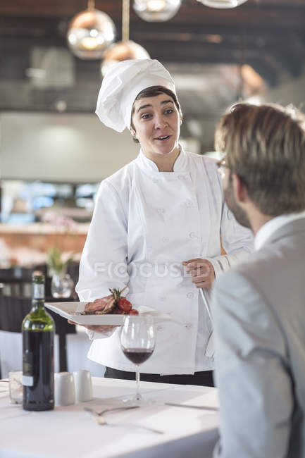 Chef serving food for businessman — Stock Photo
