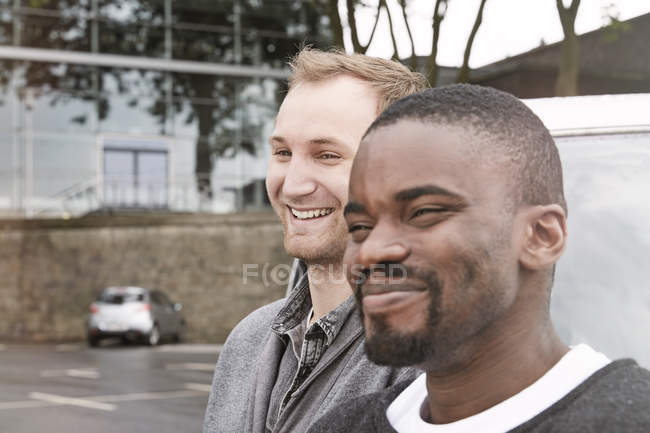 Smiling young men looking away on street — Stock Photo