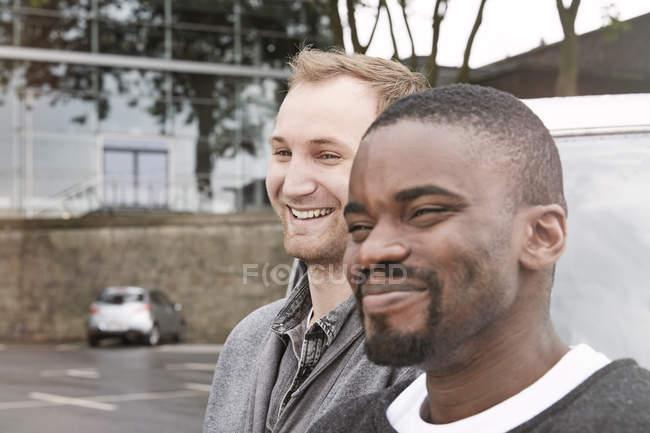 Homens jovens, olhando para longe na rua a sorrir — Fotografia de Stock
