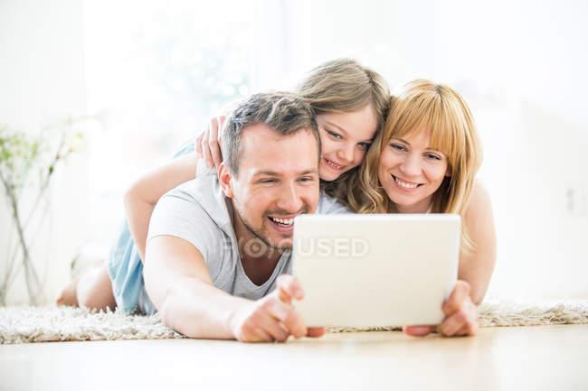 Glückliche Familie auf Boden mit digital-Tablette zu Hause — Stockfoto