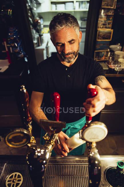 Человек, стучащий пивом в ирландском пабе — стоковое фото