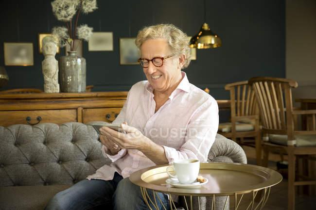 Sorridente uomo anziano in salotto utilizzando phablet — Foto stock
