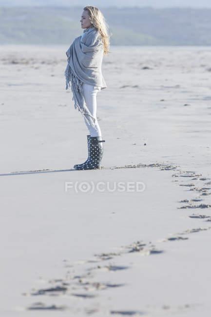 Mujer joven de pie en la playa mirando a la distancia - foto de stock