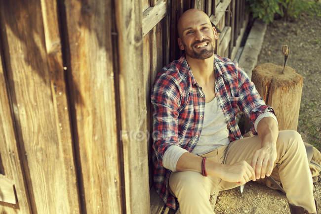 Портрет мужчины в клетчатой рубашке, сидящего перед деревянной хижиной — стоковое фото