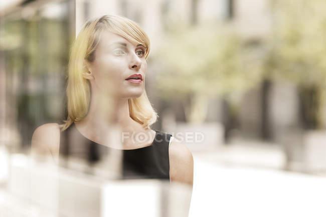 Портрет красивой блондинки-предпринимательницы за стеклом, размытый фон — стоковое фото