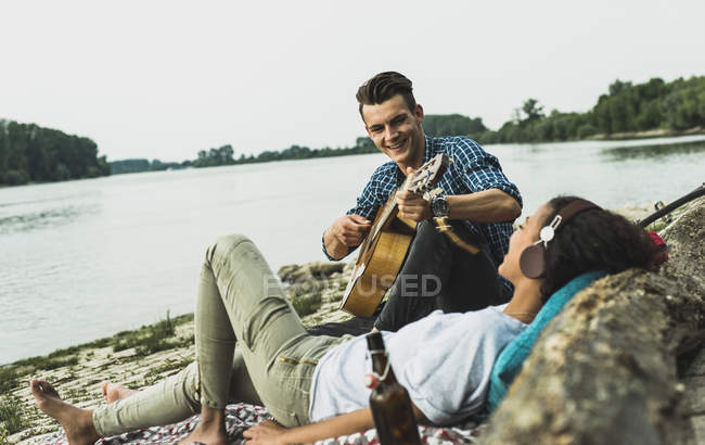 Relaxed young couple with guitar by the riverside — Stock Photo