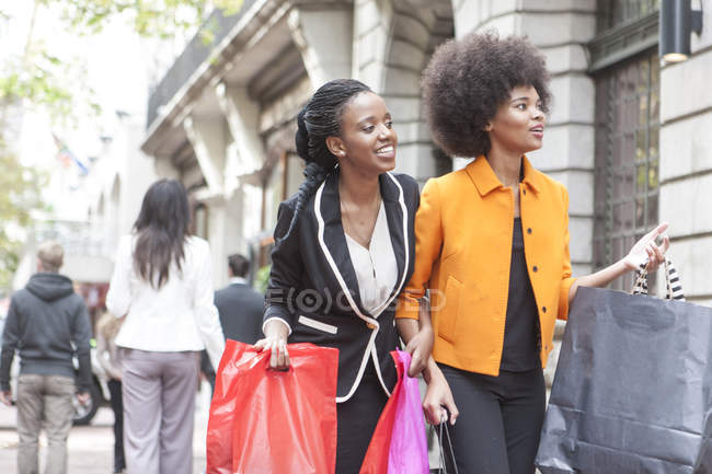 Two young women arm in arm on shopping tour — Stock Photo