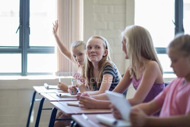 Schulmädchen in Klassenzimmer mit Mädchen, die Hand heben — Stockfoto