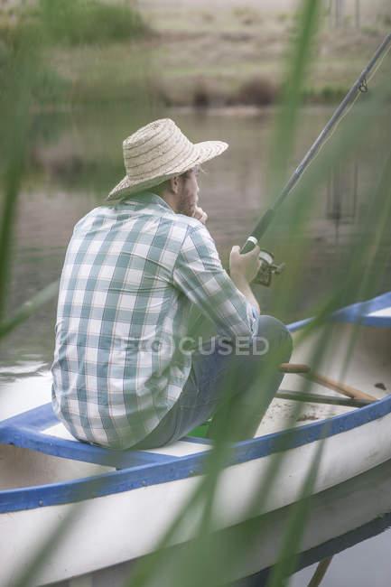 Homme assis dans un canot sur un lac de pêche — Photo de stock
