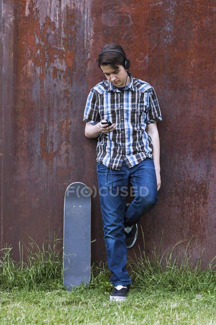 Teenage boy with skateboard leaning on corten wall hearing music — Stock Photo