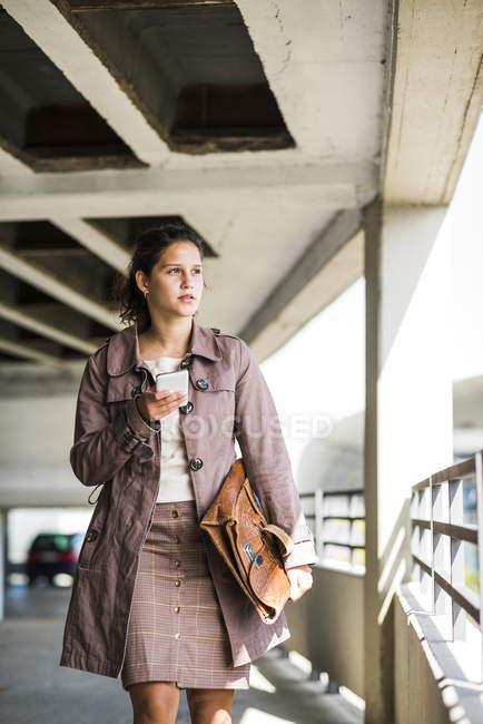 Jovem usando telefone inteligente na garagem de estacionamento — Fotografia de Stock