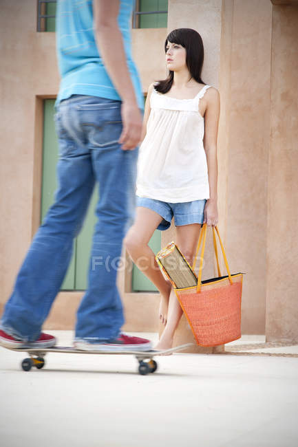 Young woman leaning against pillar while young man longboarding in the foreground — Stock Photo