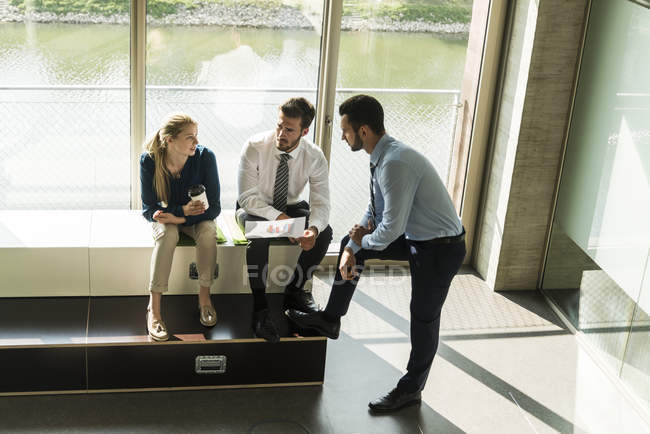 Three young business people discussing document — Stock Photo
