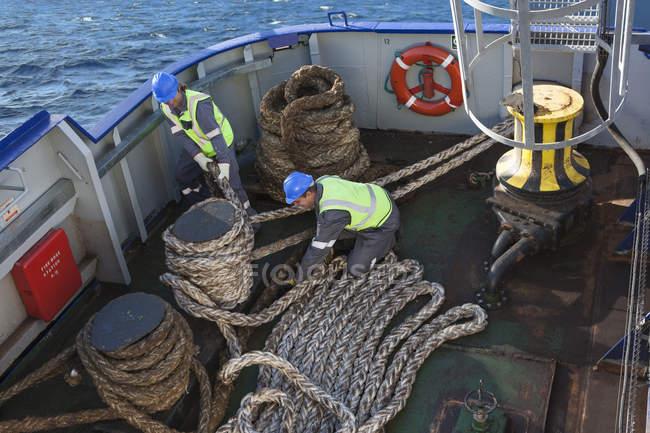 Tripulación caucásica adulta trabajando a bordo de un barco - foto de stock
