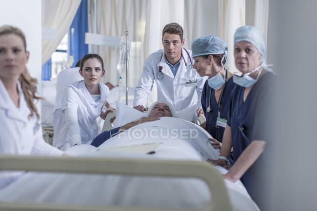 Krankenhauspersonal steht mit Patient am Bett — Stockfoto