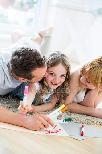 Маленька дівчинка, що лежить на підлозі з батьками, креслення з фломастери — стокове фото