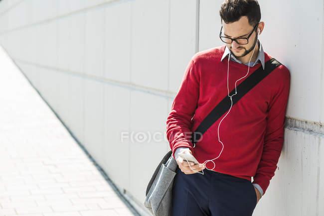 Junger Geschäftsmann mit Smartphone, trägt Kopfhörer — Stockfoto