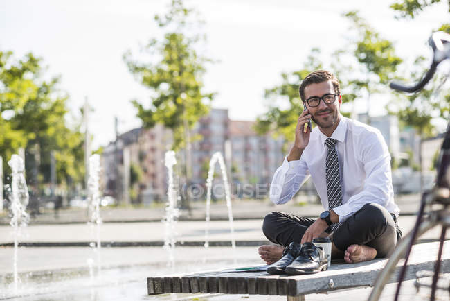 Young businessman sitting cross-legged on bench, using smartphone — Stock Photo