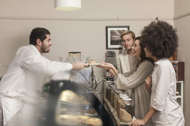 Customers queuing at cake counter in coffee shop — Stock Photo