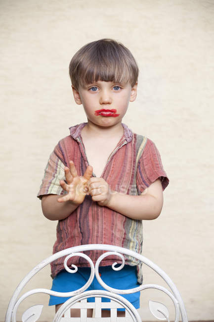 Portrait of litte boy with red lipstick on his face pouting mouth — Stock Photo