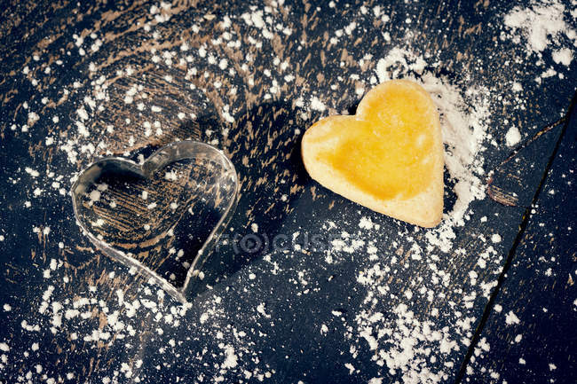 Heart-shaped Christmas cookie and cookie cutter on black wood — Stock Photo