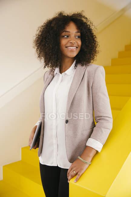 Porträt eines lächelnden Teenagers, der auf einer gelben Treppe steht — Stockfoto