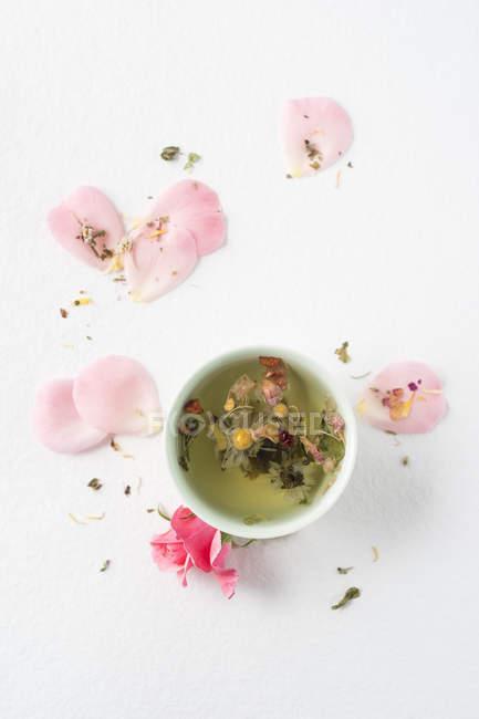 Chá de ervas com pedais de rosa, margaridas — Fotografia de Stock