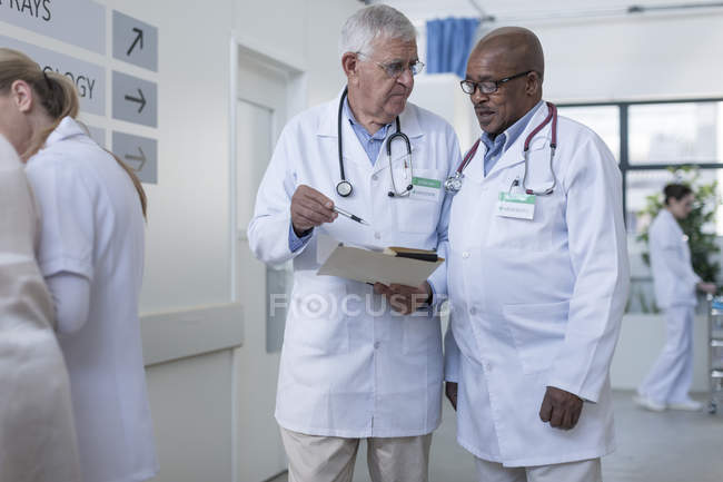 Two doctors in hospital corridor discussing patient file — Stock Photo